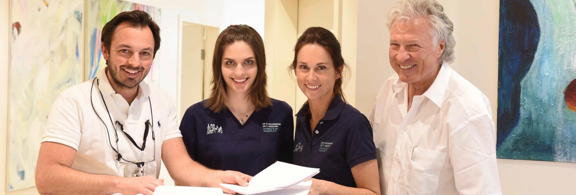 zwei Zahnärzte und zwei Zahnarzthelferinnen begrüßen ihre Patienten in einer Zahnarztpraxis in München