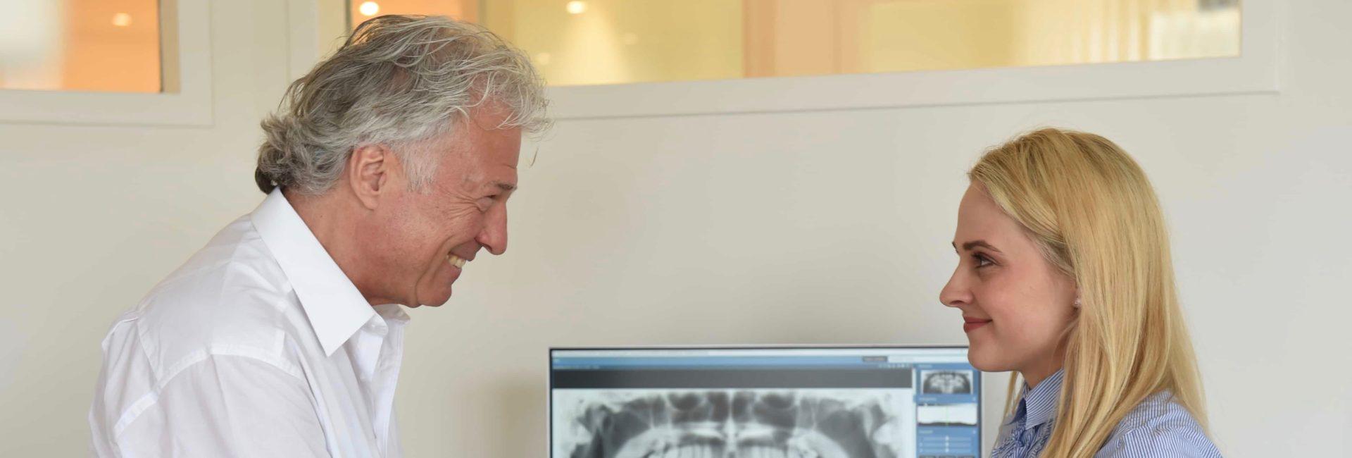 Zahnarzt Dr.Hocheneder erklärt Patientin Behandlunsbilder in Praxis am Marienplatz