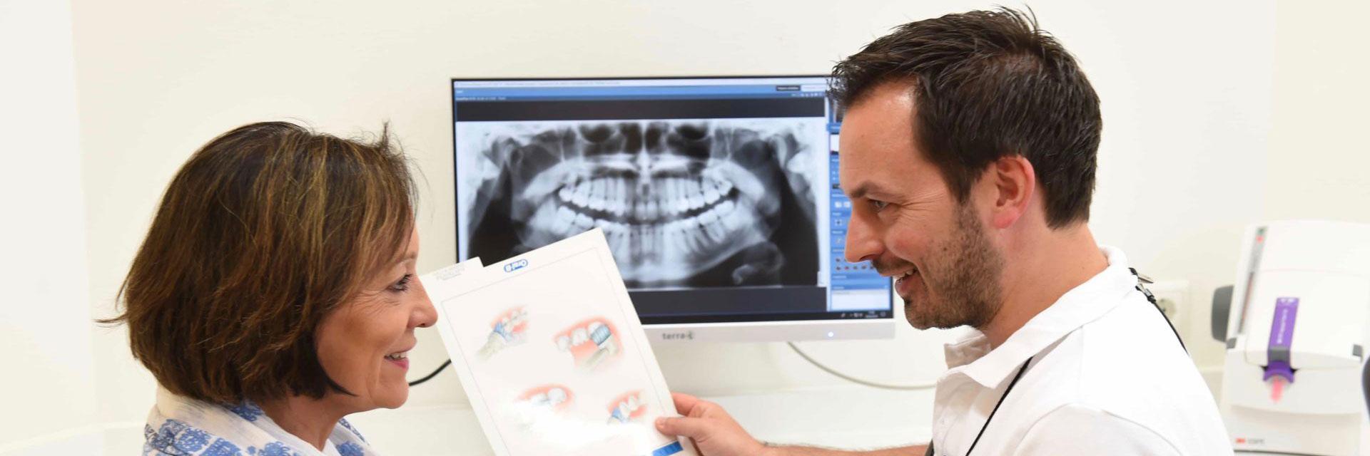 Zahnarzt Dr.Hoischen im Beratungsgespräch mit Patientin in Münchner Praxis