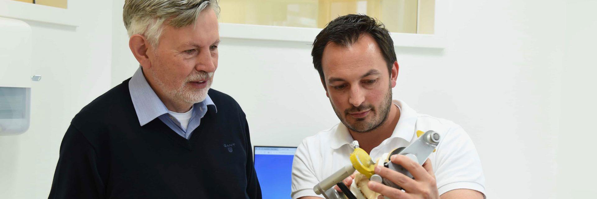 Anhand von Modellen klärt Zahnarzt Dr. Tomas Hoischen einen männlichen Patienten auf