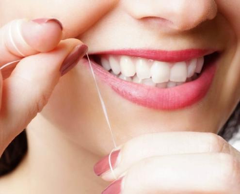 Frau bei Zahnreinigung mit Zahnseide